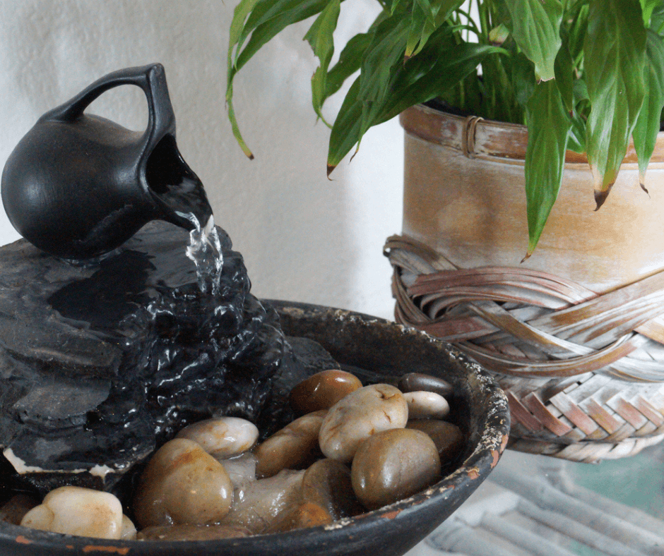 Photo of a tabletop indoor fountain and a houseplant