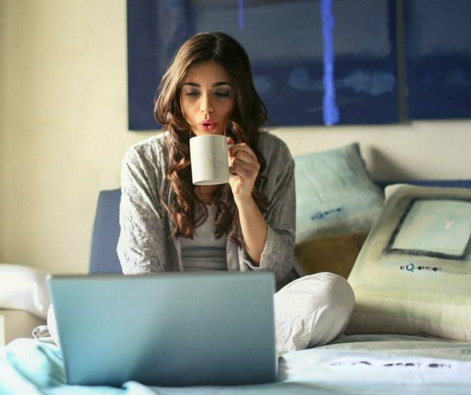 Woman sitting in bed drinking coffee and working on a laptop. Photo credit Andrea Piacquadio