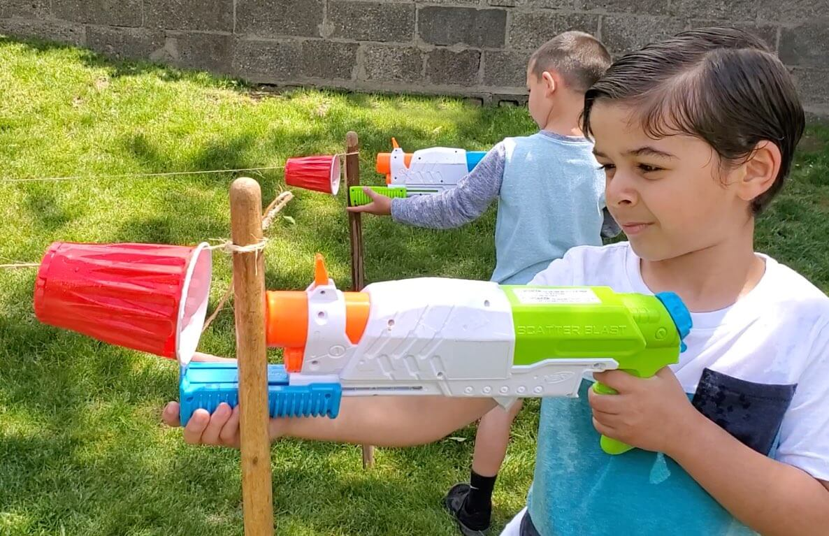 Two boys using water squirters to push plastic cups along a string.